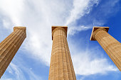 Three ancient greek pillars against blue sky