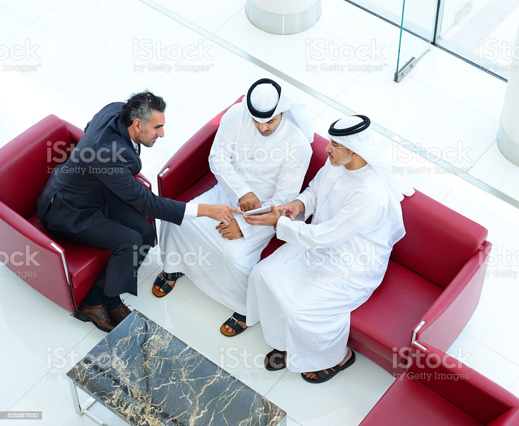 Three arab businessmen in meeting, with tablet and phones stock photo