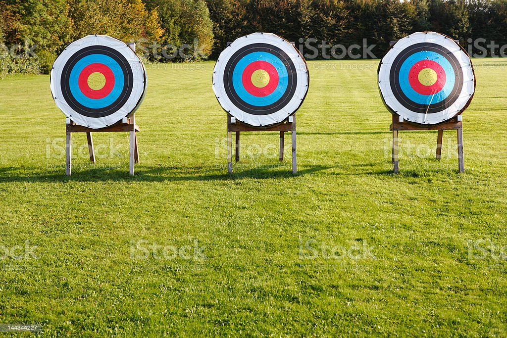 three archery targets in a row on green meadow stock photo