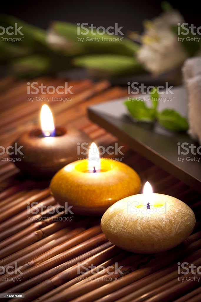 Three aromatherapy candles on a dark bamboo mat stock photo
