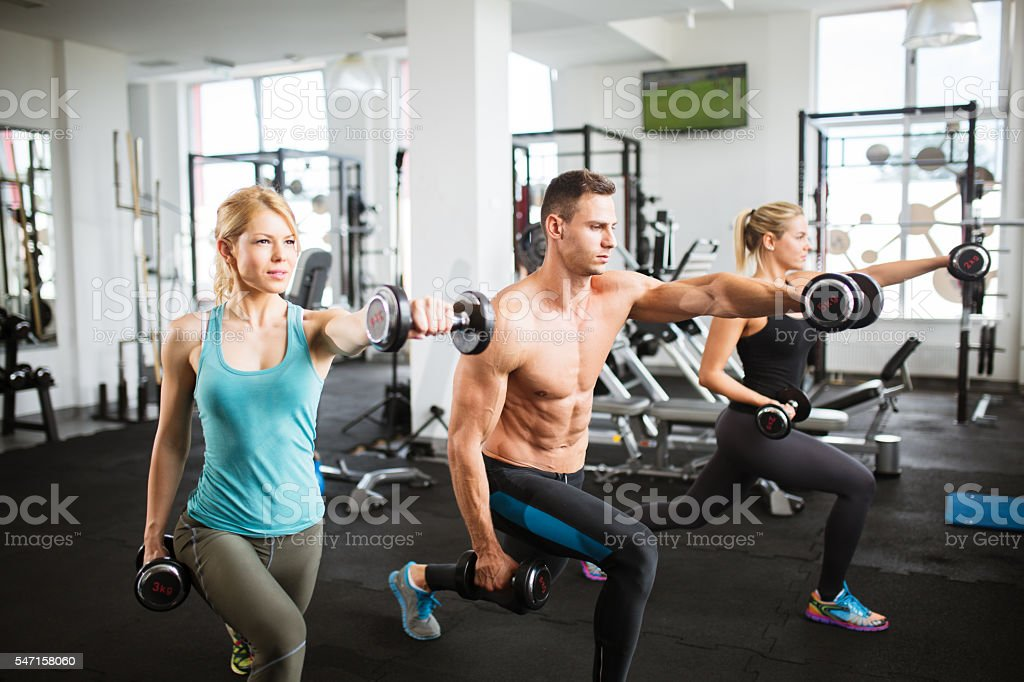 Three attractive people doing lunges with dumbbells. Side view. stock photo