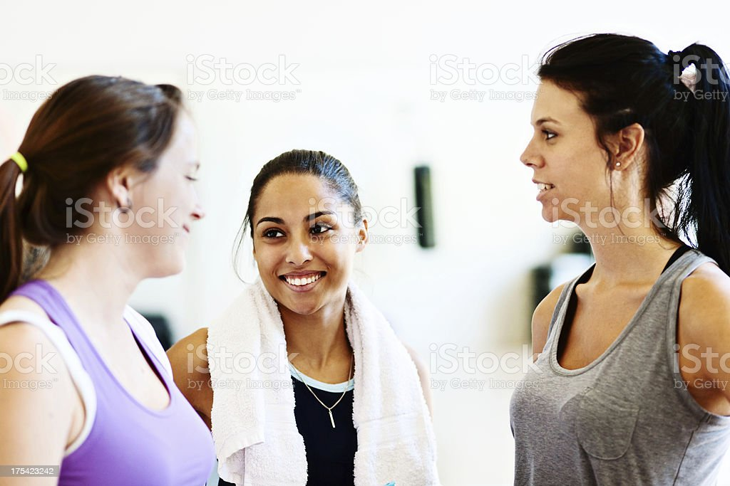 Three attractive women chat after exercising in all-female gym stock photo