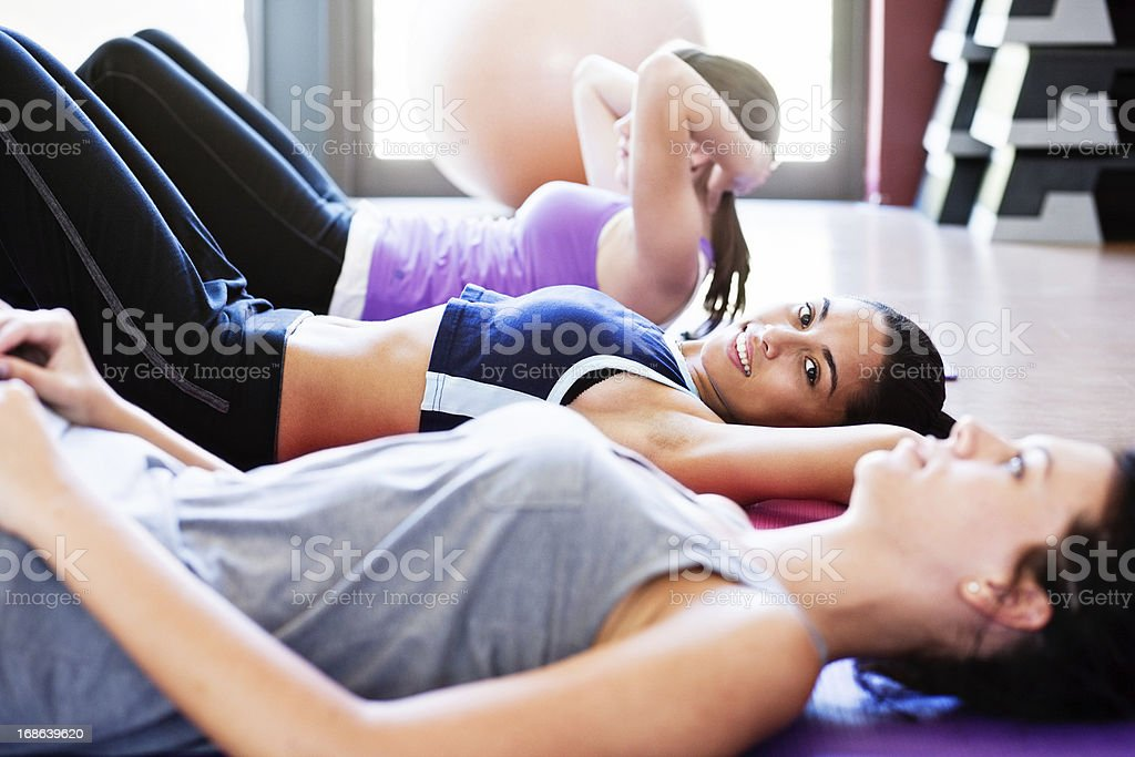 Three attractive women get fit doing sit ups in gym stock photo