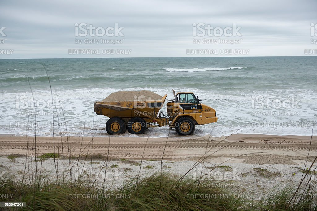 Three axle articulated truck moving sand on eroded beach stock photo