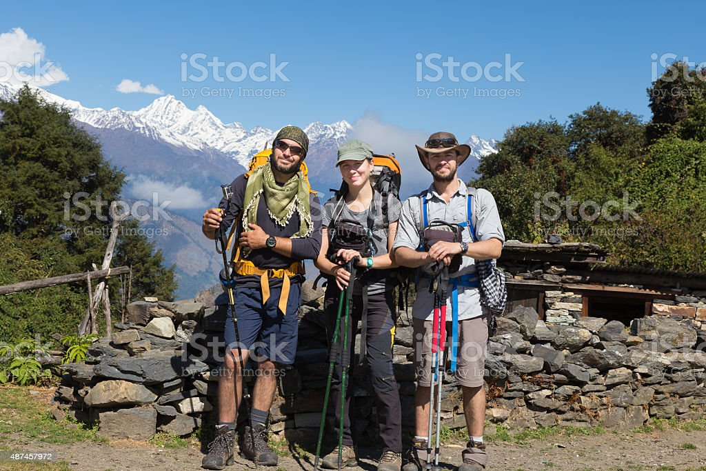 Three backpackers tourists posing, snow mountains peaks ridge. stock photo