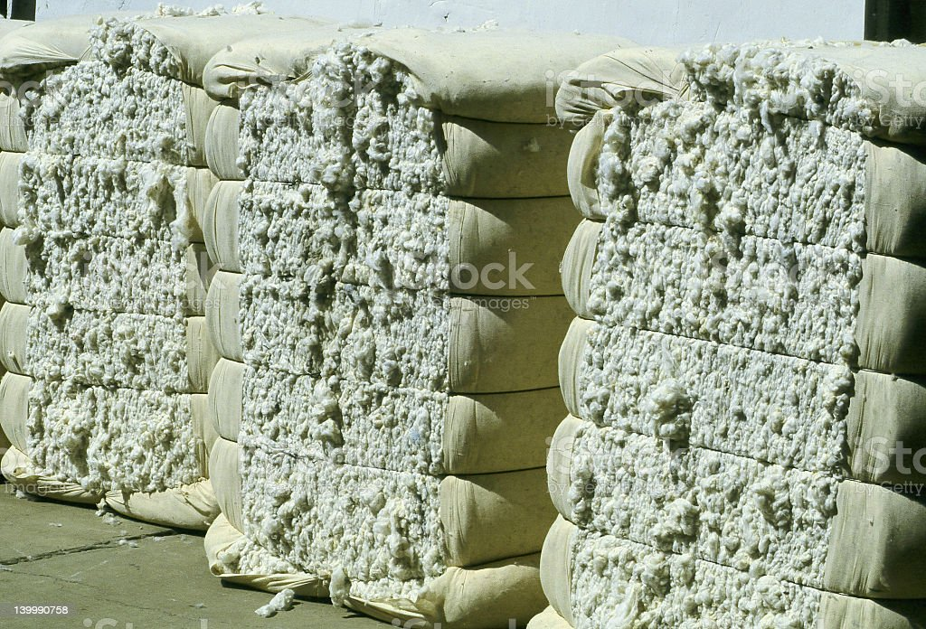 Three bales of cotton sitting on cement stock photo