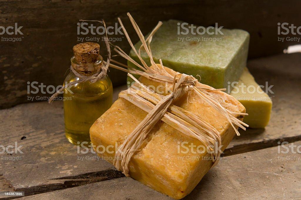 Three bars of natural soap and a jar of oil royalty-free stock photo