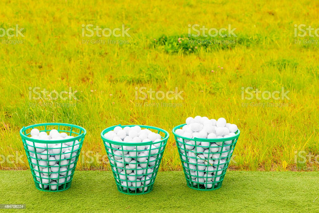 three baskets filled with golf balls on the green grass stock photo