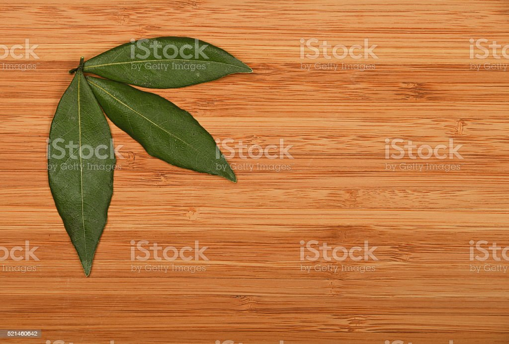 Three bay leaves in bamboo wooden board corner royalty-free stock photo