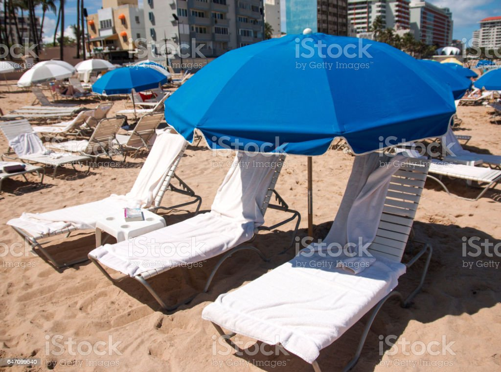 Three beach chairs and a blue umbrella on the sand stock photo