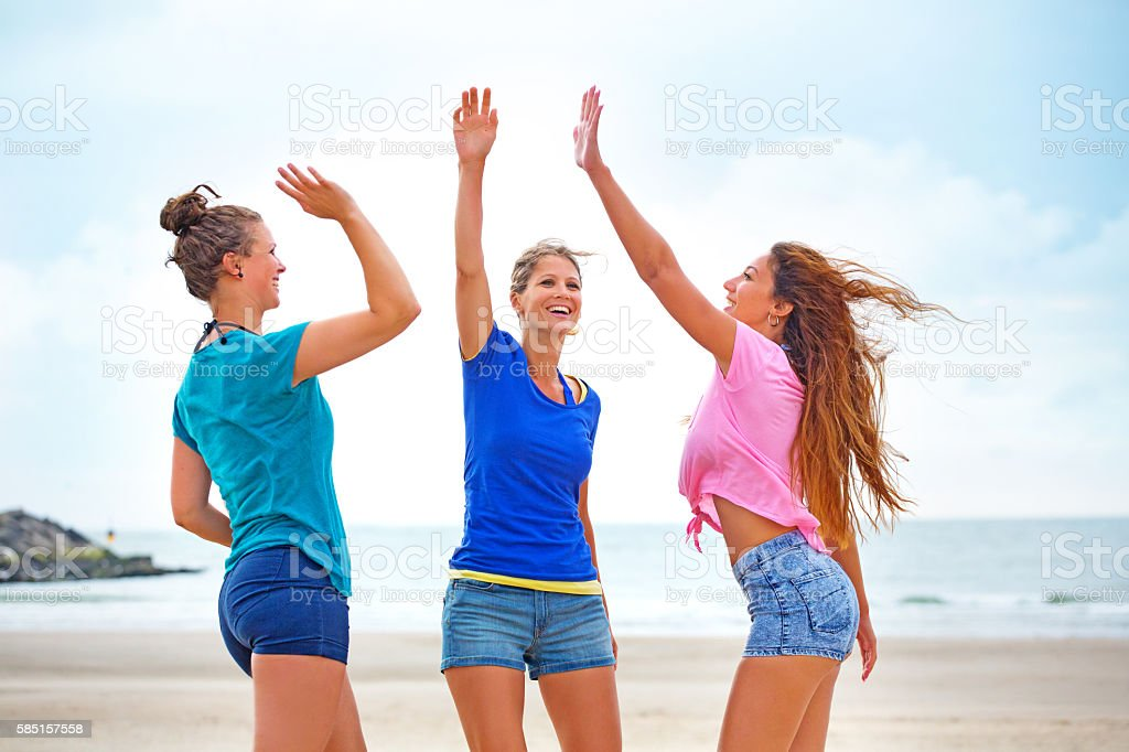 Three beautiful casual female friends celebrating on a beach stock photo