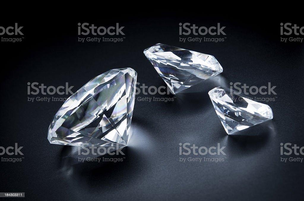 Three beautiful diamonds on a black background. stock photo