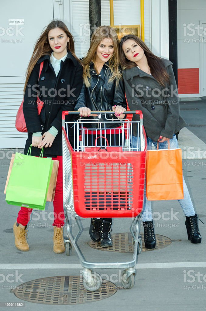 Three beautiful girls and a shopping trolley stock photo
