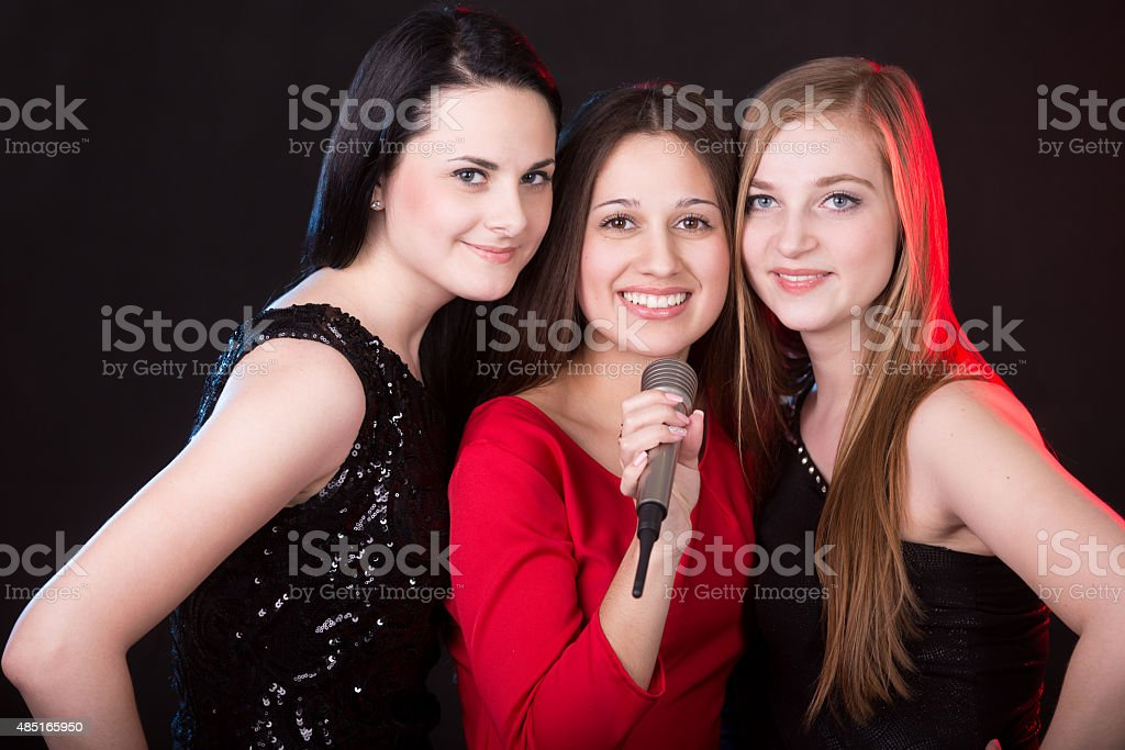 Three beautiful girls with microphone stock photo