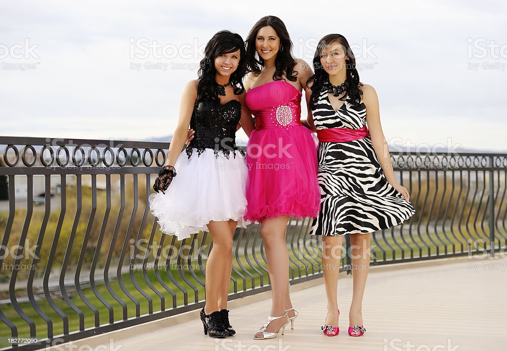 Three Beautiful Teenagers In Formals Standing On A Balcony Together stock photo