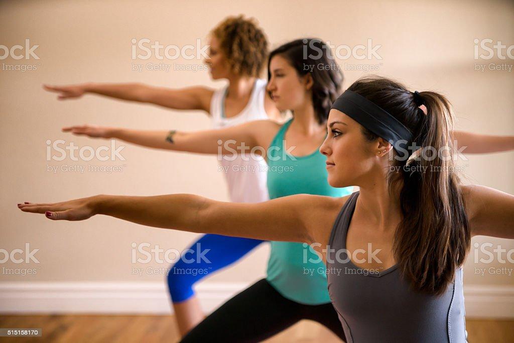 Three Beautiful Women Doing Yoga Indoors stock photo