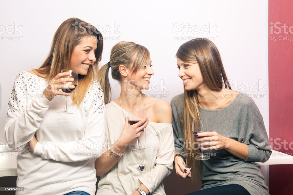 Three beautiful women friends talking and drinking red wine royalty-free stock photo
