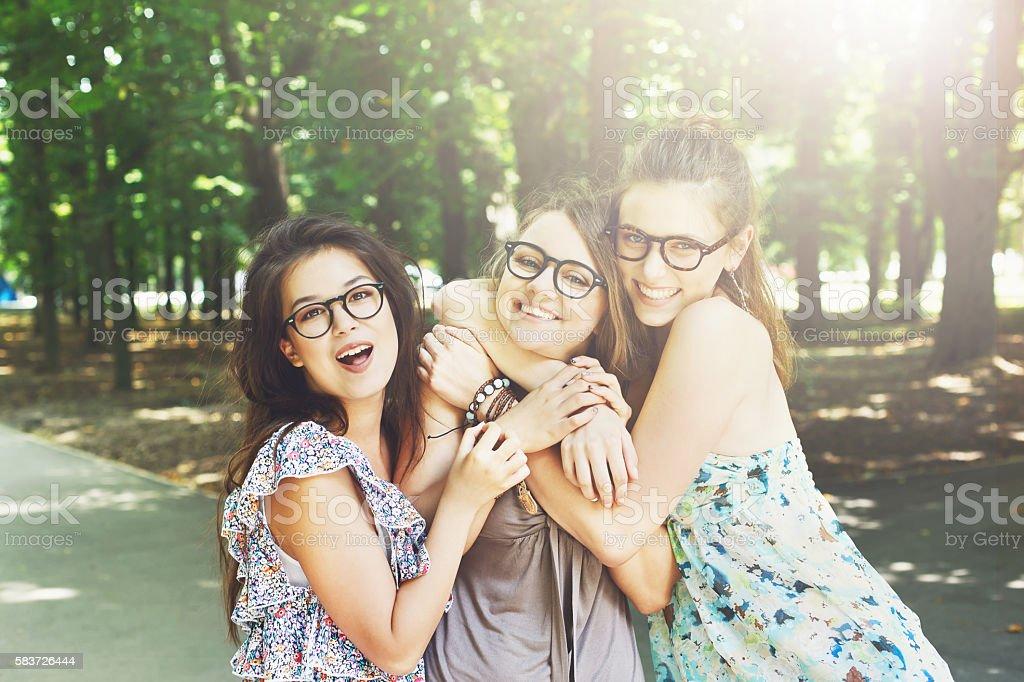 Three beautiful young boho chic stylish girls walking in park. stock photo