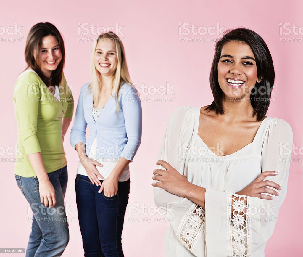 Three beautiful young women stand together laughing royalty-free stock photo