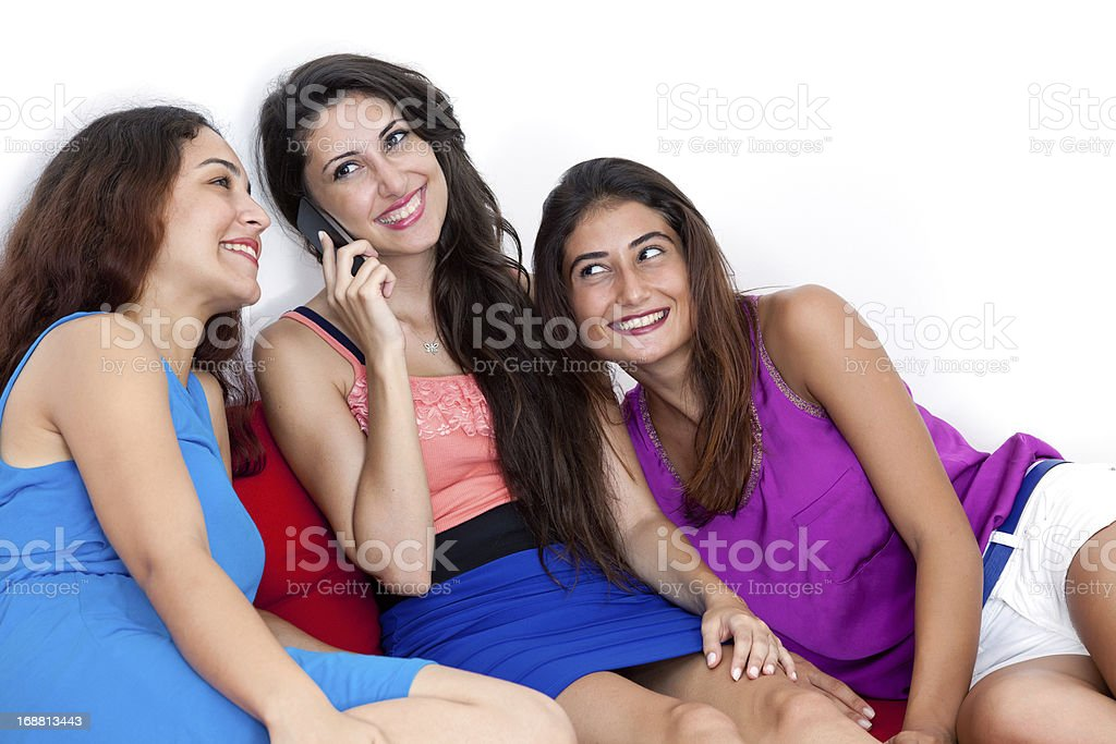 Three beautiful young women with a smart cell phone. royalty-free stock photo