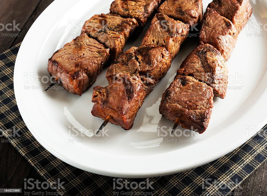 Three beef kebabs arranged on a white platter royalty-free stock photo