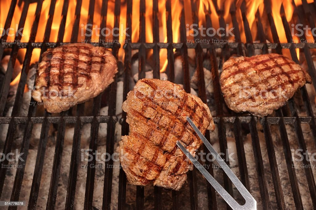 Three Beef Steaks On The Hot BBQ Flaming Grill stock photo