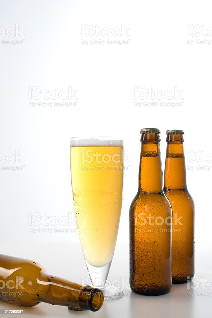 Three beer bottles and a glass full of beer. stock photo