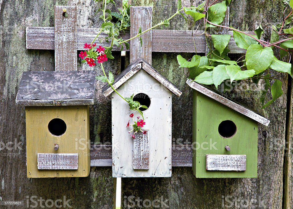 Three birdhouses on old  wooden fence stock photo