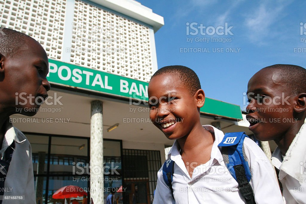 Three black African senior schoolboys, talk on the street. stock photo