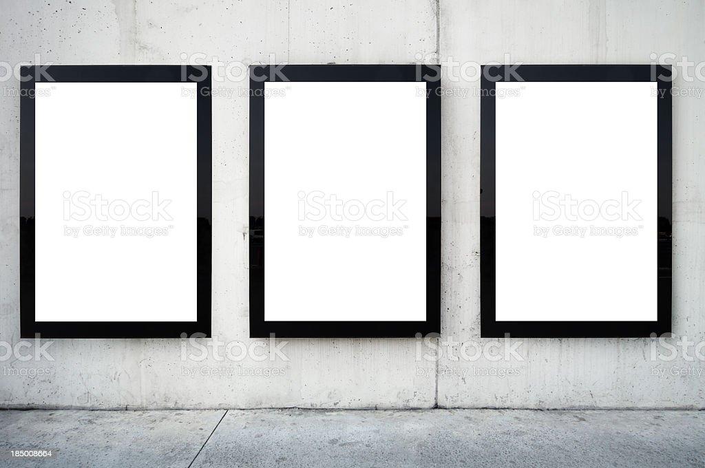Three blank billboards on wall. stock photo
