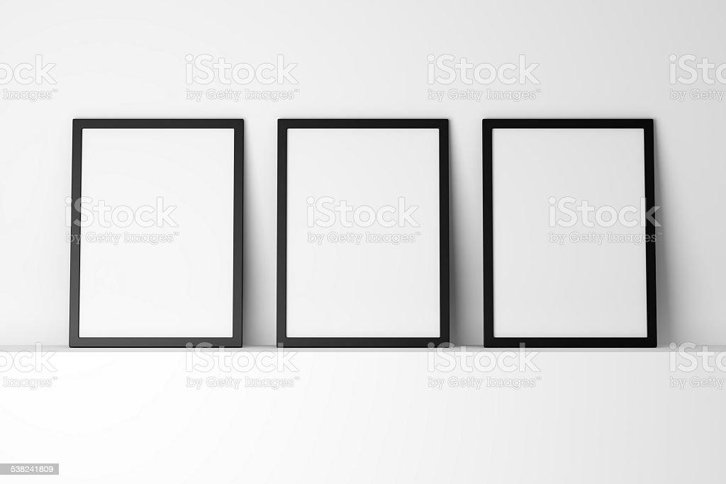 three blank black photo frames on white shelf stock photo