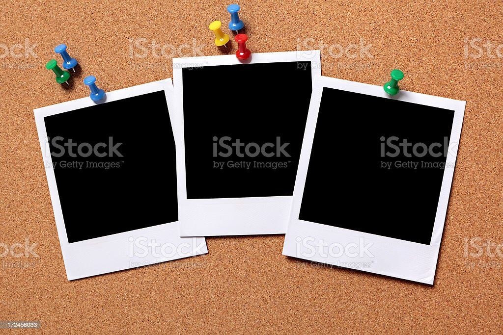 Three blank photos pinned to a cork board royalty-free stock photo