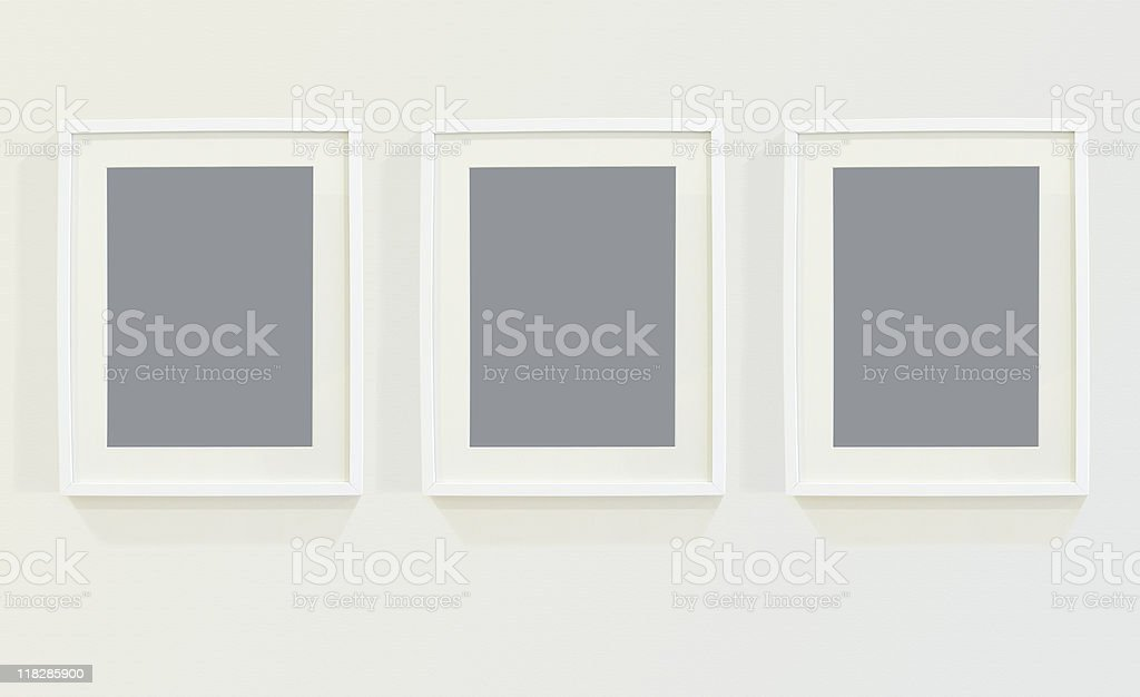 Three blank picture frames hanging on a wall in a row royalty-free stock photo