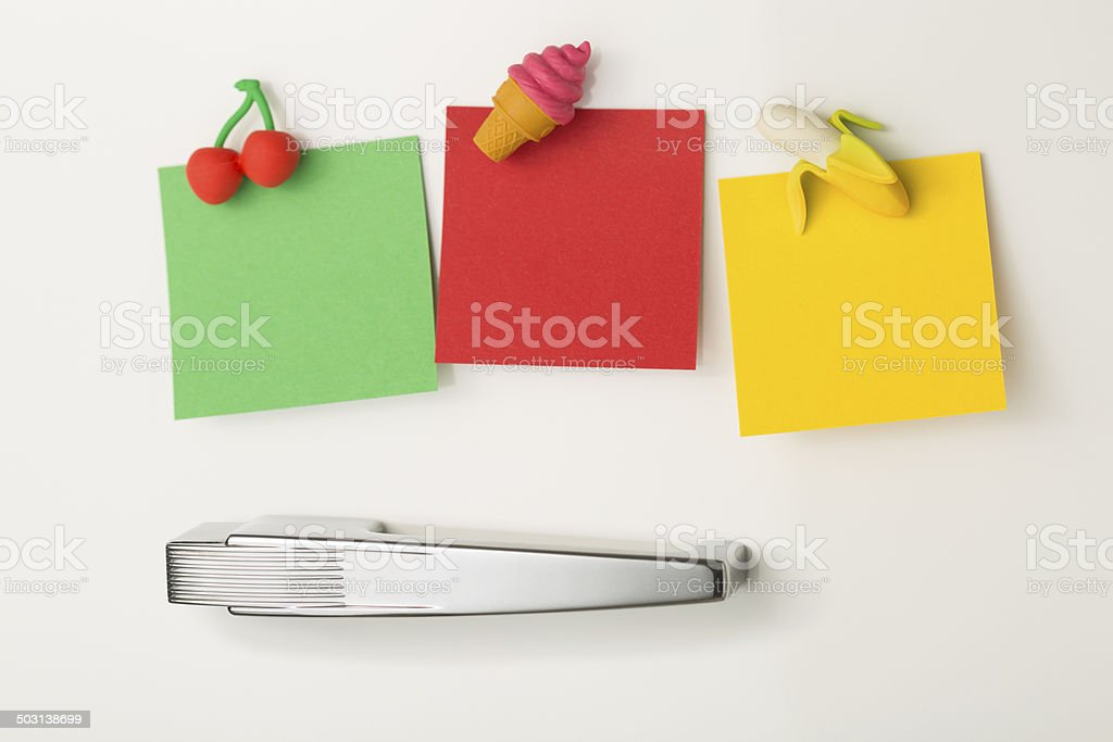 Three blank post-it notes attached to refrigerator with fridge magnets stock photo