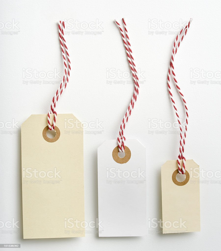 Three blank tags in various sizes with red striped string stock photo