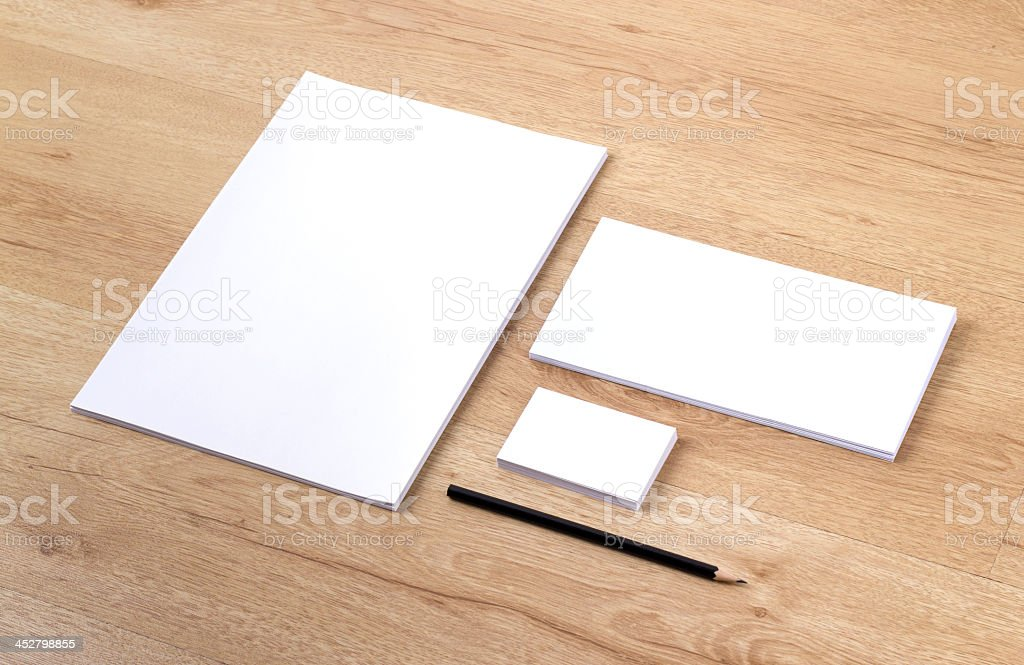 Three blank white notepads with black pencil on wooden table stock photo
