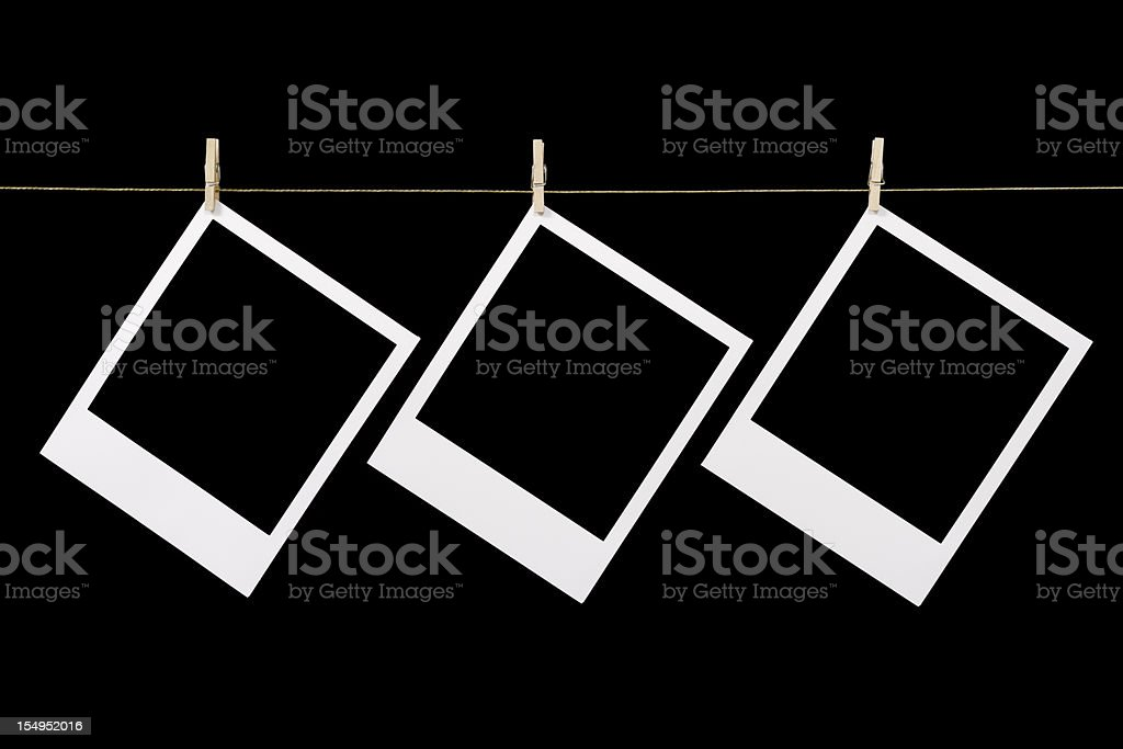 three blanked-out polaroid instant photographs hanging royalty-free stock photo
