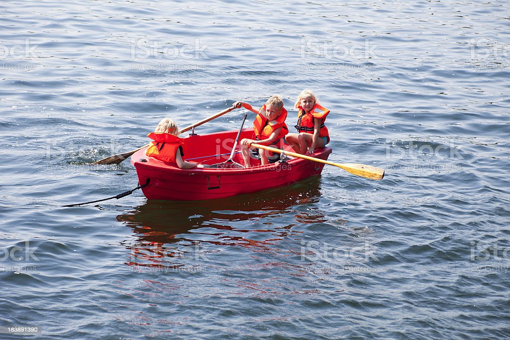 Three blond children in a red boat on the sea. royalty-free stock photo