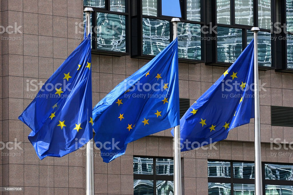 Three blue and yellow European flags blowing on poles royalty-free stock photo