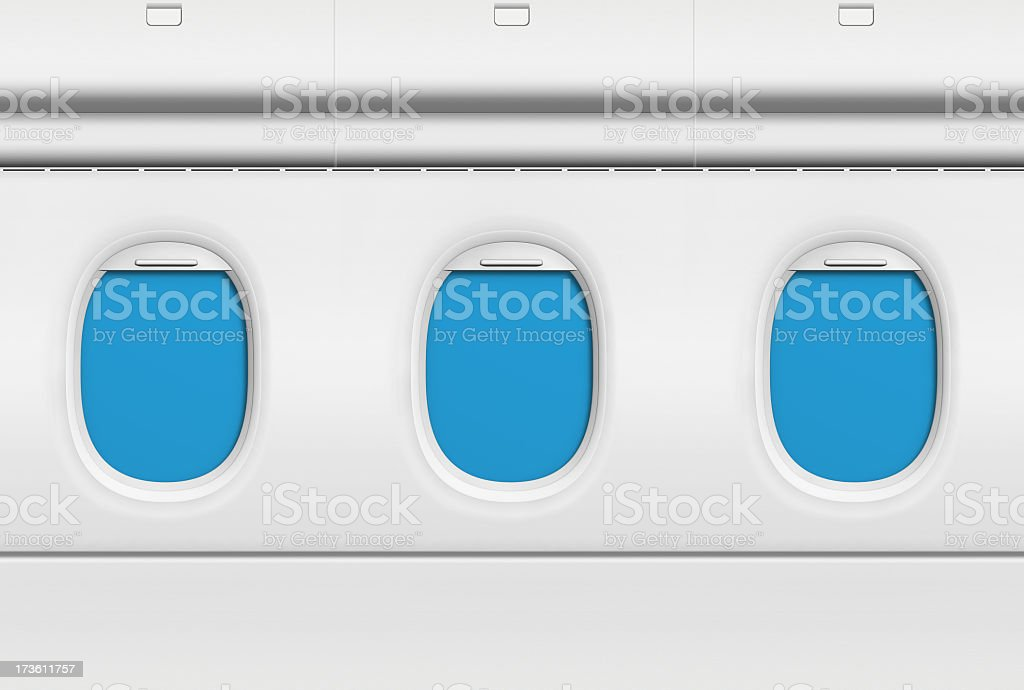 Three blue covered airplane portholes stock photo