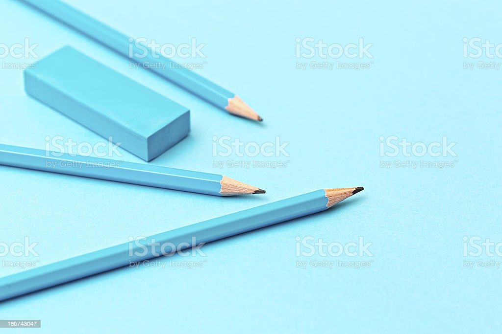 Three blue pencils and a blue pencil sharpener on a matching blue...