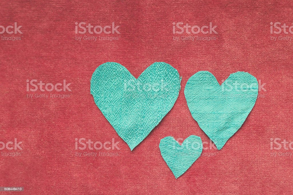Three blue silk hearts on red velvet background stock photo