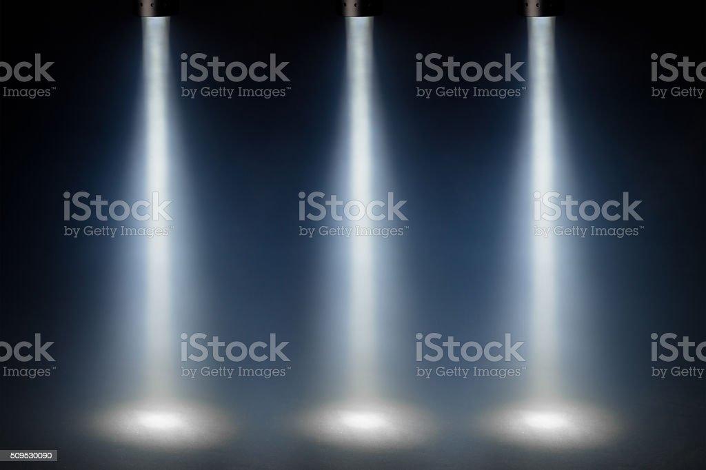 three blue spot lights on stage stock photo