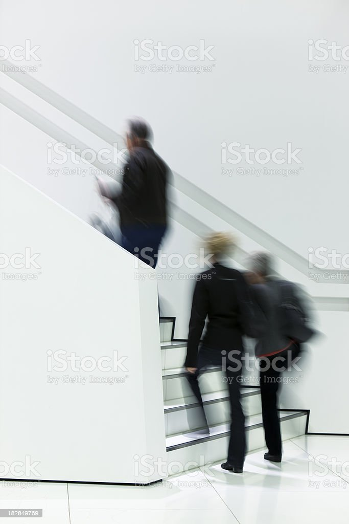 Three Blurred Persons Walking Up White Stairs royalty-free stock photo