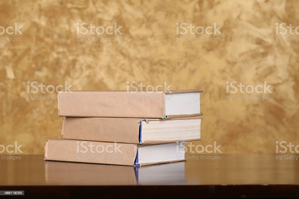 Three books lying on the wooden table and brown background stock photo