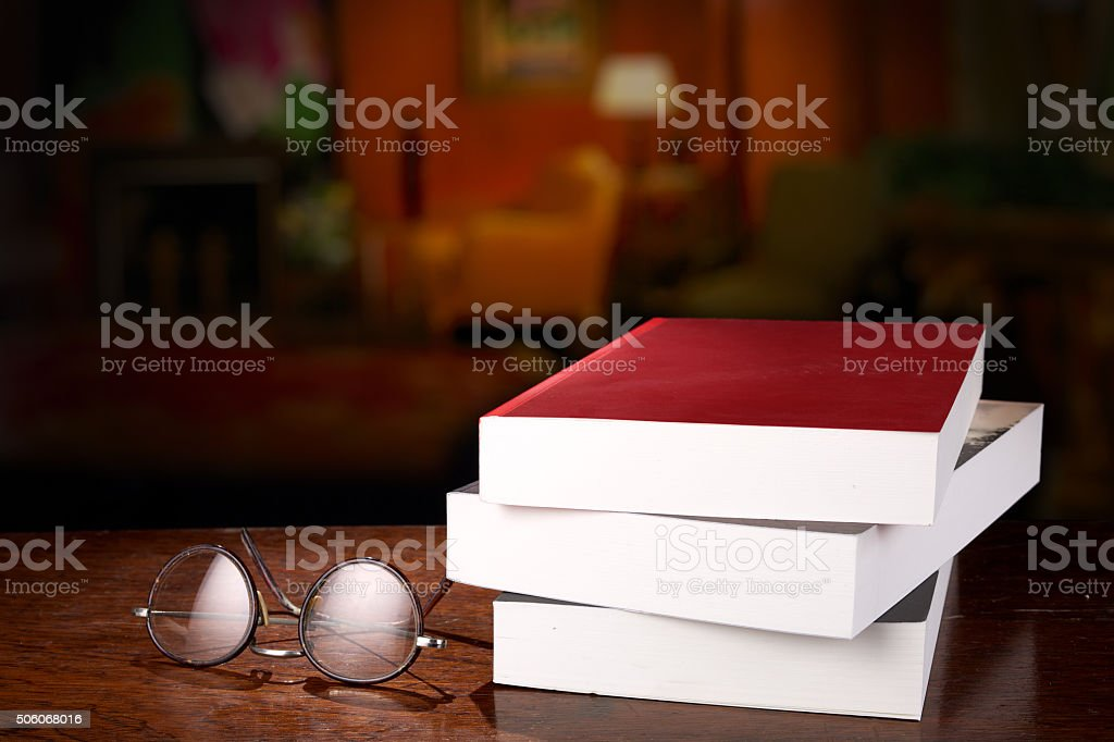 Three books on a desk stock photo