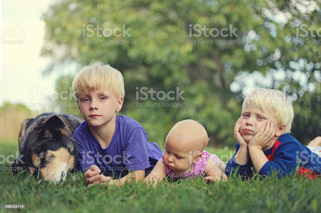 Three Bored Young Children and Dog Relaxing Outside stock photo