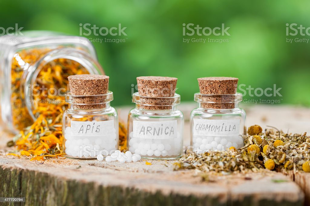 Three bottles of homeopathy globules and healthy herbs. stock photo