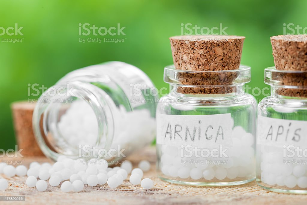 Three bottles of homeopathy globules stock photo
