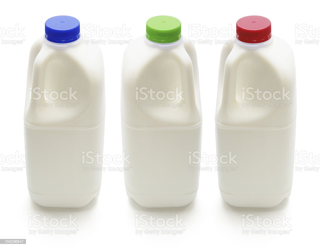 Three bottles of milk with different colored caps stock photo